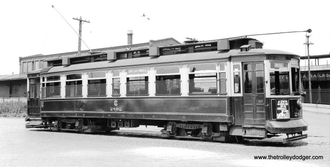 """CSL 2802 is on Anthony Avenue at Commercial Avenue in this July 13, 1941 photo. Note the Pennsylvania Railroad station at rear. (John F. Bromley Collection) Bob Laich: """"The building immediately behind CSL 2802 on Anthony Avenue was PRR's South Chicago freight station, which was built at street level. The platform for the South Chicago passenger station can be seen on the elevation in the right background."""" Andre Kristopans adds, """"something odd here – note """"Special"""" sign in front window. Appears to be a charter waiting for its party off the PRR."""" This must be Central Electric Railfans' Association fantrip #35, which used this car on that date."""