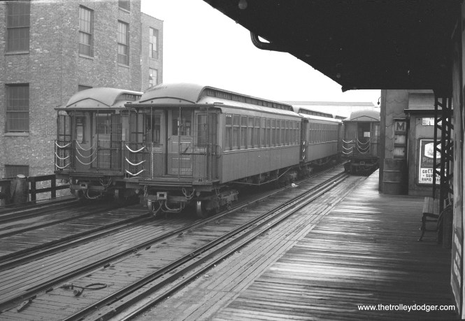 "Where this picture could have been taken was somewhat of a mystery, but the one place that seems a good fit is the old Lawndale terminal on the Humboldt Park ""L"". There, only one track served the platform, while there were two tracks for storage. Gate cars such as these were used during the CTA era, and the ""L"" itself was shoehorned between buildings such as the one at left. There was a tower at the end of the platform, such as the one seen here. In that scenario, the ""M"" may simply stand for Metropolitan, as Humboldt Park was part of the Met ""L""."