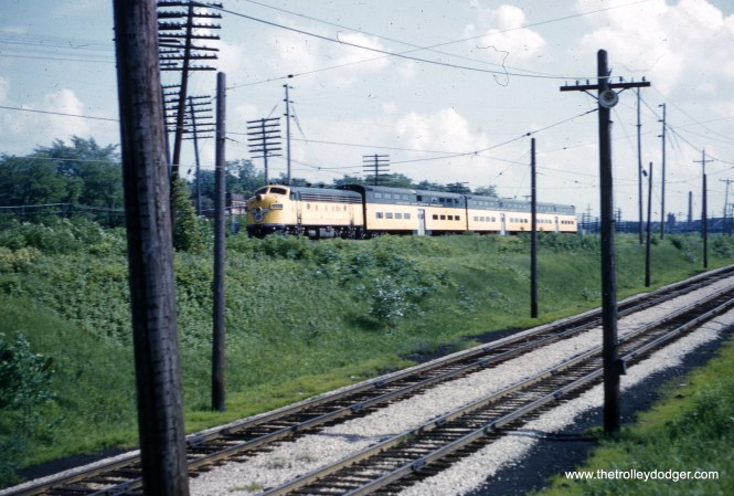"""This photo of a Chicago & North Western train of bi-levels was taken by Al Clum in June 1962. But where? One reader writes, """"The descending tracks in the foreground of the photo are leading to the North Shore Line's North Chicago Junction Station. The CNW train is on the CNW embankment between Great Lakes to the south and North Chicago to the north. Since the headlights are not turned on on the locomotive, one would presume that the train is a push-pull heading south."""""""