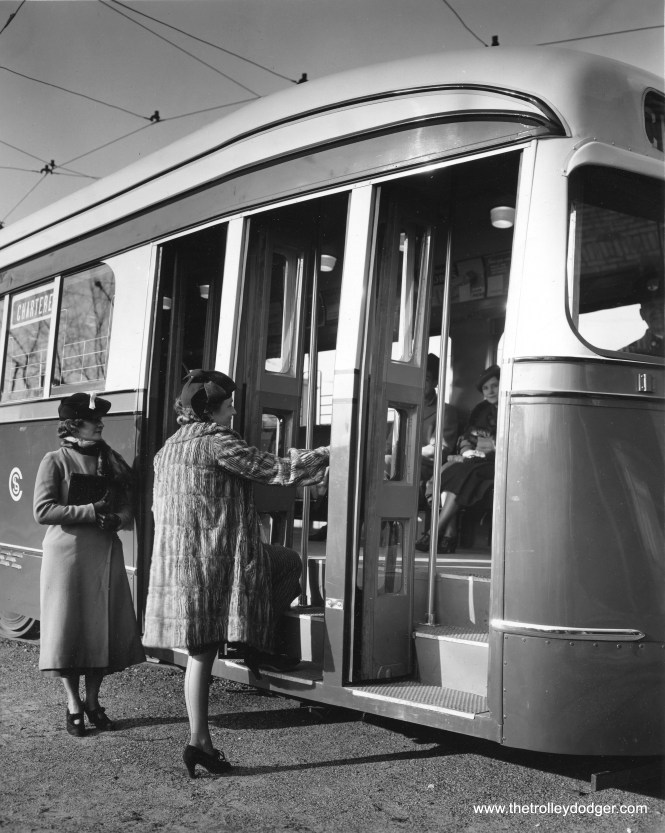 """In this posed press photo, probably taken in late 1936, two well-dressed models show how easy it is to get on the new """"streamliners."""" This may be car 7002. (Chicago Architectural Photographing Company)"""