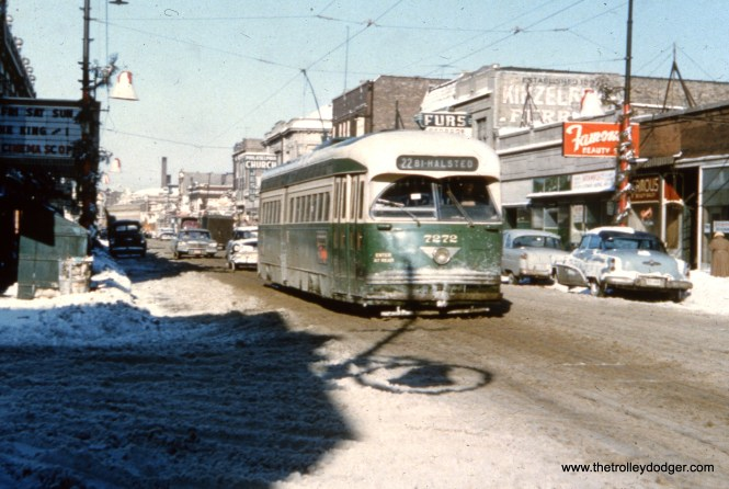 """It's winter, and CTA 7272 heads south. The local movie theater is showing The King and I, a musical starring Yul Brynner that was first released in June 1956. This picture probably dates to the winter of 1956-57, and there is a 1957 Plymouth visible at rear. One of our readers notes: """"The movie theater was the CALO THEATER at Clark and Balmoral. It is now occupied by a thrift store called The Brown Elephant. Photo was probably taken in December 1956 because of the Christmas decorations hanging on the line poles. Car is heading south on Clark."""" You can read more about the Calo Theater here."""