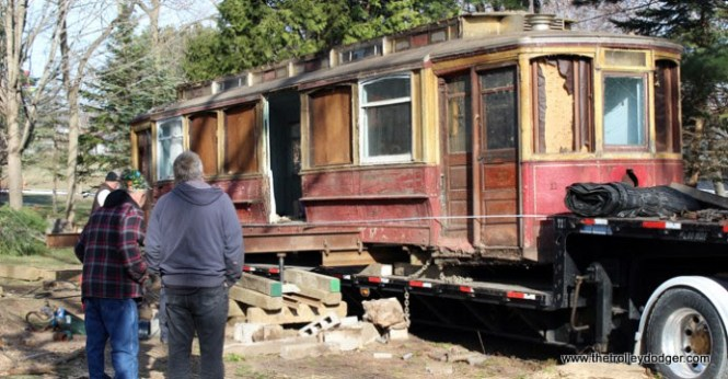 Frank Sirinek (left) and Jay Drouillard watch as preparations continue for moving the trolley out of Sharon and Bill Krapil's backyard in Weyauwega. (Angie Landsverk Photo)