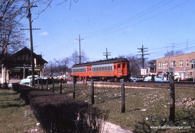 """This undated 1950s photo shows a westbound Chicago, Aurora & Elgin train (cars 406 and 41x) at the Villa Park station. According to the Great Third Rail web site, """"The station was rebuilt again in 1929. During this reconstruction, the eastbound platform was moved to the west side of Villa Avenue with the construction of an expansive Tudor Revival station designed by Samuel Insull's staff architect, Arthur U. Gerber. The westbound platform remained in place and was outfitted with a flat roofed wooden passenger shelter. Villa Park was one of a few stations to survive the demise of the Chicago, Aurora and Elgin. Both it and Ardmore (the next station west) were purchased by the village of Villa Park and refurbished with an official dedication by the Villa Park Bicentennial Commission on July 5, 1976. It is now home to the Villa Park Historical Society which hosts an annual ice cream social on July 3, the anniversary of the day the CA&E ended passenger service."""""""