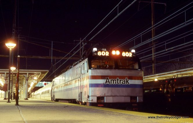 On February 9, 2002 I was out riding and photographing trains on Amtrak's North East Corridor. After riding all day and as as night approached, I arrived at Trenton NJ on a SEPTA train. My intent was to catch a connecting NJ Transit train to continue east and head for home. As luck would have it, a Conrail train snagged and pulled down the catenary wires somewhere close by and just like that, the trains stopped running. I was stranded for a while so I took advantage of the situation and started taking night photos. I had no tripod so I had to make do with what was available, like taking off my shoe and putting the camera in it! This photo shows Amtrak E-60 # 602 with Train # 40 the THREE RIVERS stopped at Trenton. It is illuminated by the headlight of a NJT train.
