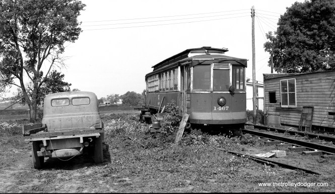 "It's May 30, 1958 and Chicago Surface Lines car 1467 (former CTA salt car AA72) is at the Electric Railway Historical Society site on Plainfield Road in Downer's Grove. Don's Rail Photos says this ""Bowling Alley"" car ""was built by CUTCo in 1900 as CUT 4516. It was rebuilt as 1467 in 1911 and became CSL 1467 in 1914. It was rebuilt as salt car and renumbered AA72 on April 15, 1948. It was retired on February 28, 1958. It was sold to Electric Railway Historical Society in 1959 and went to Illinois Railway Museum in 1973."" Actually it must have been sold earlier, as the negative envelope has written on it ""owned now by ERHS!"" (Bob Selle Photo)"