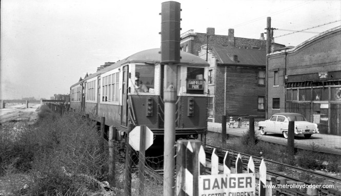 "Some railfans would not have taken this picture, due to the position of the signal, which obstructs the view of the train. But it does give you an idea of how ""L"" train movements were hampered during the nearly five years of operation on temporary trackage along Van Buren Street from 1953 to 1958. As the expressway, to the left, appears unfinished, I would guess this picture dates to around 1954. All trains had to come to a complete stop at each intersection, which is likely how that signal operates. I believe the cross street here is Western Avenue, and we are facing west. (Walter Hulseweder Photo)"