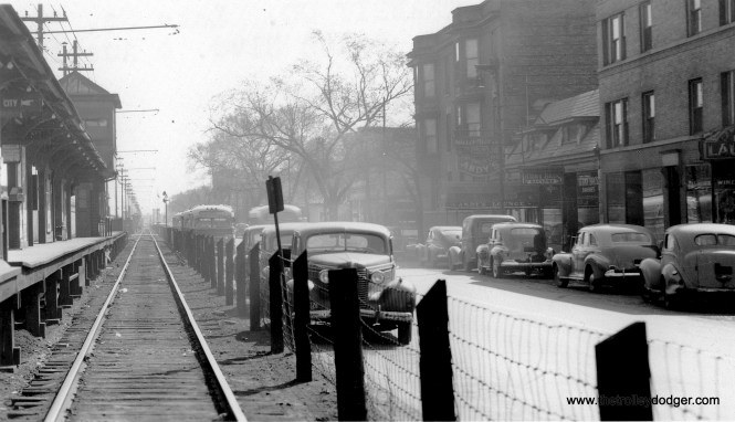 "Here's an interesting streetscape that could not be duplicated today. According to the back of the picture, it shows the view looking east from South Boulevard and Austin, on the eastern edge of Oak Park. The Lake Street ""L"", where it ran on the ground, had a very narrow right-of-way that the 6000s, with their bulging sides, could not fit in. So, looking for a place to build space for CRT/CTA employee use, there was nowhere to go but up. Not sure which bus routes are there in back, but this was the Chicago side of the street, which would argue against West Towns. It must be Chicago, since Oak Park was ""dry"" at the time and liquor is being sold. Bill Shapotkin adds: ""If this is indeed at Austin (and I believe it is), the street is still called Lake (NOT South Blvd -- as I understand that is strictly an Oak Park name). There were de facto two Lake Streets at this point-- one north of the C&NW and one south of the C&NW. The name ""Corcoran"" (again as I understand it) did not come along until possibly the time the 'L' was rerouted onto the C&NW embankment). As for the bus -- probably a W/B E16 -- Lake. The bus looped via W/B Lake-N/B Austin-E/B Lake-S/B Mayfield-E/B Lake. That said, there appears to be a bus heading E/B as well -- and that I cannot explain."" George Trapp adds, ""Lake Street photo at South Blvd. and Austin, buses are Chicago Motor Coach TD-4502's at terminal of Route 31 Washington Blvd. Buses are in their original 1940 paint jobs so photo dates to 1940's."" (George Trapp Collection)"