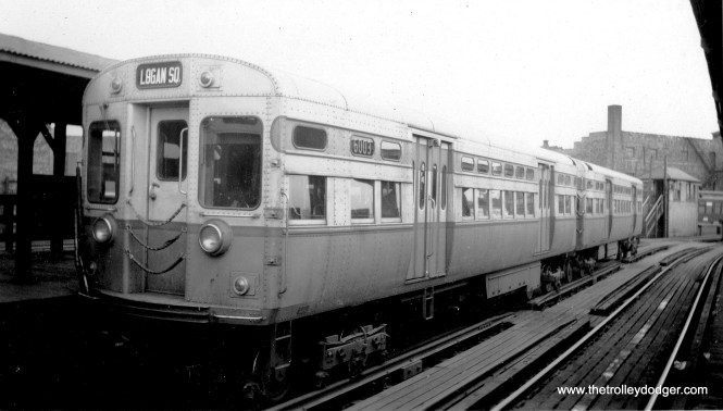 "CTA ""flat door"" cars 6003-6004 at Logan Square in the 1950s. Note the slightly different paint scheme compared to later cars in this series. George Trapp: ""6003-6004 at Logan Square, in addition to the different paint scheme from 6005-6130, notice extra metal sheets riveted to large window posts between 1st and 2nd windows from each end. Only 6001-6004 had them."" (George Trapp Collection)"