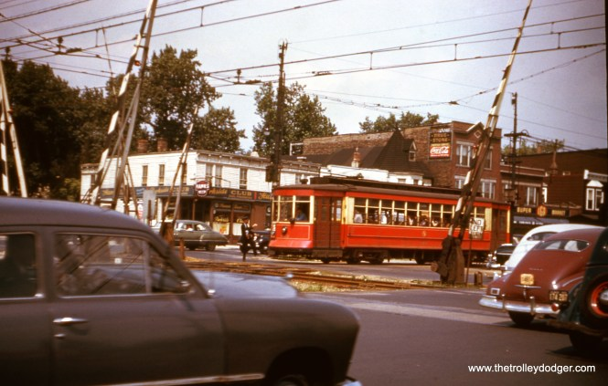 """CTA Pullman 812 crossing the Illinois Central Electric suburban service in August 1948. Not sure which line this is. Bill Shapotkin: """"As for the """"line"""" (presume you mean the IC, not CSL/CTA line), the one in the next photo is the IC South Chicago line. The carline is Stony Island."""" M. E. writes, """"I blew up this photo to read the destination sign. It seems to say 28 Stony Island, 93rd. If so, then this view is at 71st and Stony Island, and the streetcar is heading south. It was probably just south of 71st St. that Stony Island became very wide, with a private right-of-way for streetcars right down the middle of the street, then grassy swales on either side of the streetcar path, then one-way auto traffic on each side of the swales. I'm pretty sure this separation existed at 75th St. You see this private right-of-way in your photo here. Confirmation is at https://en.wikipedia.org/wiki/South_Shore,_Chicago where one paragraph states: Before the community came to be known as South Shore in the 1920s, it was a collection of settlements in southern Hyde Park Township. The names of these settlements—Essex, Bryn Mawr, Parkside, Cheltenham Beach, and Windsor Park—indicate the British heritage of the Illinois Central Railroad and steel mill workers who had come to inhabit them. Most of these settlements were already in place when the Illinois Central built the South Kenwood Station in 1881 at what is now 71st and Jeffrey Boulevard."""" Tony Waller: """"The photo at 71st & Stony Island could have been of a Stony Island car or a Windsor Park car, as the latter line diverged from Stony Island at 73rd St."""" David Vartanoff: """"pic of 812 might well be Stony Island and 71st. clues are, median streetcar ROW, and the name Parkside on the corner building. Parkside was the original name of the IC station at Stony Island."""" Bob Lalich: """"I agree. The view is NW."""""""