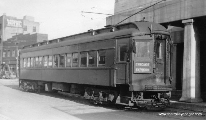 """Chicago, Aurora & Elgin car 107 under trolley wire in downtown Aurora in 1936. Within a short period of time, the street running in Aurora was eliminated and replaced by a new terminal with private right-of-way. Don's Rail Photos: """"107 was built by Stephenson in 1903. It was wrecked in 1914 and rebuilt as an express trailer. It was retired in 1937."""" I'm not sure if this is really car 107 (as the photo says it is), since this car looks like it can run under its own power, which an express trailer could not do. Andre Kristopans: """"CAE car in Aurora – probably 407. 107 was a woodie to begin with!"""" Don's Rail Photos says, """"407 was built by Pullman in 1923."""" Bill Shapotkin adds, """"This pic is indeed in Broadway at the CB&Q overcrossing (just south of Benson). When the streetcars quit in Aurora, the car tracks (which had at one time gone under the CB&Q) were cut-back to this point. The view looks N/E."""""""