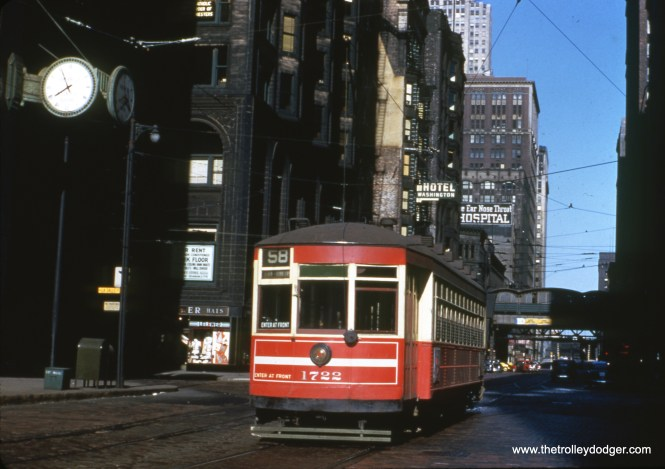 "One-man car 1722 is on Washington at LaSalle in downtown Chicago, running route 58 (Ogden). George Foelschow: ""Red car 1722 is westbound on Washington Street at LaSalle Street. The building on the left with arches and bay windows is genius starchitect Louis Sullivan's Stock Exchange Building now, sadly, demolished. Photographer Richard Nickel was killed when documenting demolition and the floor above him collapsed. The stock trading room as well as the main entrance were saved and can be visited at the Art Institute."" Kevin Doerksen: ""One-man car 1722 is on Washington. The Chicago Eye, Ear Nose and Throat Hospital, pictured in the background, was located at 258 W Washington (at Franklin)."""