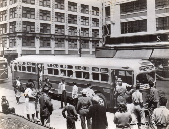 "In this tricked-up photo, we see a GM demo bus, the design of which eventually became the 500 series, at an unidentified location (not Chicago) circa 1950. George Trapp adds, ""The bus is the GM Model TDH5502 Demo which became Chicago Motor Coach #500 in 1951. This bus may have been the first paired window version of the Yellow/GM so called ""Old Look"" buses. It differed somewhat from the production buses #501-600 delivered from Oct. - Dec. 1948. The demo lacks the ""Michigan marker lights"" front and rear and has two rectangular shaped vents between the headlights which the 501-600 lacked. The CMC TDH5103's 601-650 of 1950 and 651-700 of late 1951 as well as Fifth Avenue Coach TDH-5104's of 1952 also lacked them."" Dan Cluely adds, ""I believe that the demo bus picture is downtown Pontiac MI. The S.S. Kresge store seem to match, and this would only be a short distance from GM's bus plant."""