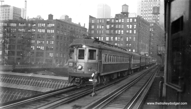 """CA&E 428, an outbound Elgin Limited, passes over Union Station on the Met """"L"""". Looks like this picture was taken from a passing car heading east."""