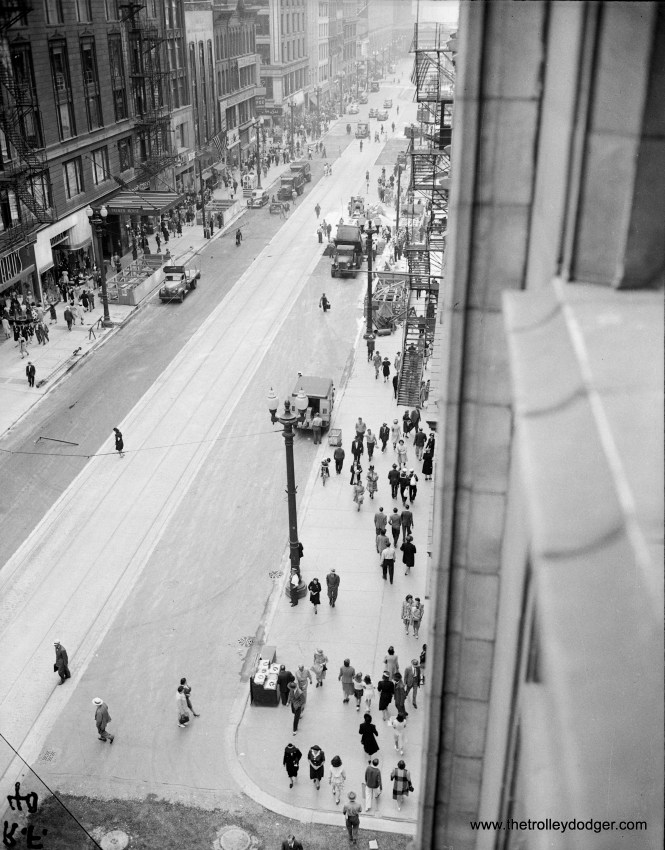 Here, we are looking south on State Street from Monroe in 1942. Construction of the State Street Subway is being finished up, with the construction of stairway entrances. New streetcar tracks have been set in concrete, while it looks like some street paving work is still going on. The famous Palmer House is at left. There are a few references to WWII visible, meaning this picture was taken after Pearl Harbor. The subway was put into regular service on October 17, 1943.