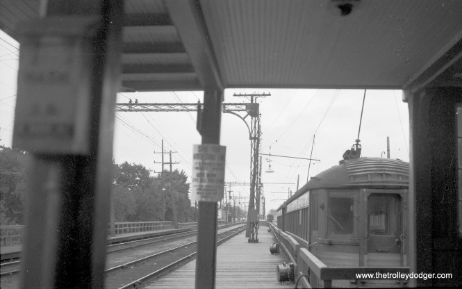 """View of two passenger interurban cars on side track for local southbound loading at Edison Court, Waukegan, Ill. Note sign on post, ""Save Your North Shore Line."" Photo taken circa 1960 by Richard H. Young. Ultimately, these efforts failed, but the demise of the North Shore Line (and the Chicago Aurora & Elgin) helped spur the Federal Government into action to begin subsidizing transit across the country."