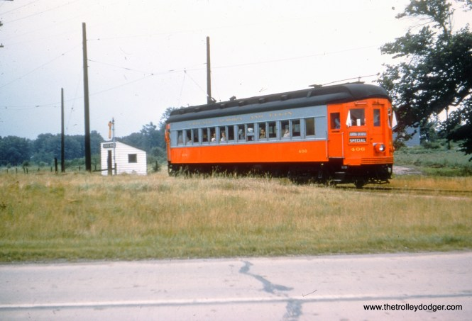 CA&E 406 in fantrip service at State Road on the Batavia branch. Due to the width of the crossing, trains switched from third rail to overhead wire at this location.