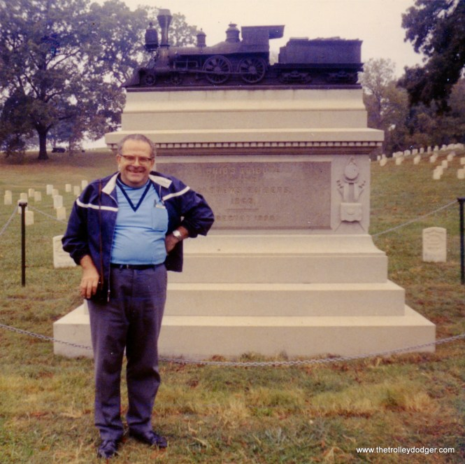 """Marvin C. Kruse at the Andrews Raiders Memorial in the Chattanooga Military Cemetery on October 23, 1907. According to Find-a-Grave: :""""Memorial erected by the State of Ohio to the Andrews Raiders. In early April, 1862, a band of Union soldiers lead by civilian James Andrews infiltrated south from the Union lines near Shelbyville, Tennessee and met at Big Shanty, Georgia (near Marietta). On the morning of April 12, 1862, 20 of them (2 raiders never arrived and 2 others overslept and missed the adventure) stole the passenger train """"The General"""" during its morning breakfast stop. With the farms and factories of Georgia supplying the Confederate Army fighting further west, the Raiders' mission was to burn the railroad bridges between Atlanta and Chattanooga, thus isolating the Confederate Armies from their supply sources and enabling the Union Army to seize Chattanooga. Due primarily to the persistency of William Fuller, conductor of the stolen train, and, secondarily to the rainy weather and unlucky miscoordination with the Union Army to the west, the Raiders failed. All 22 at Big Shanty that morning were captured. Eight, including James Andrews, were tried and hanged by the Confederate Army in Atlanta. In 1866, after the war, they were reburied in a semi-circle at the Chattanooga National Cemetery. On the imposing granite monument, erected in 1891, are the names of 22 of the raiders. The memorial is topped by a bronze likeness of the """"General""""."""" This story inspired the classic 1927 Buster Keaton film The General."""