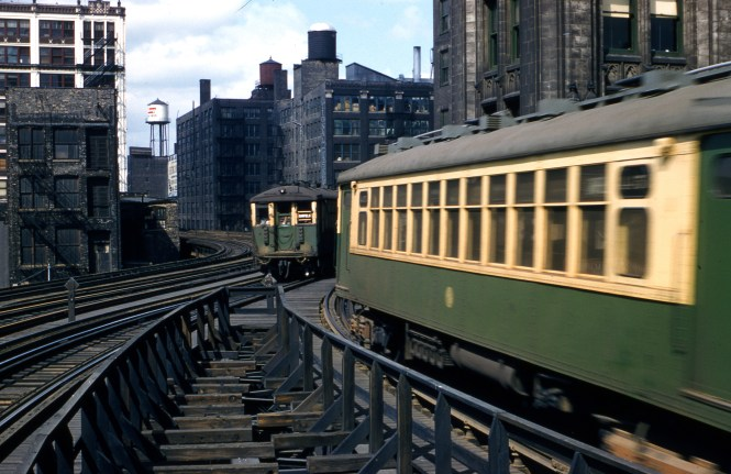"This view of two Garfield Park ""L"" trains is somewhere west of the Loop and was taken on April 13, 1957."
