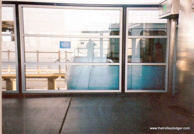 Reflections of a railfan taking a picture of the people mover at the SFO International Airport.