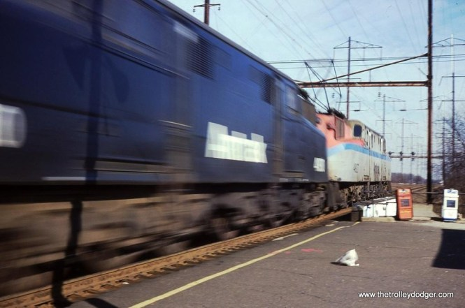 Photo 2. I took this photo of an Amtrak train powered by two GG-1s in Edison, New Jersey on December 1, 1980. I was only 17 years old at the time and was using an Electra 135 range finder camera. It was aperture priority so I could not select the shutter speed. I was told that on a sunny day to use an aperture of F5.6 or F8, which I did. I loaded a roll of Kodachrome 64 slide film into the camera and headed trackside to the Edison station. This being one of the fastest pieces of track in the whole country, combined with a camera that automatically picked shutter speeds and, using ASA 64 film, meant the results were going to be predictable. Most of the trains appeared as blurry messes! I was disappointed with this shot and stored it away for many years. I now like the shot very much! It has just the right amount of blur to convey motion but not enough to ruin the shot. Even the newspaper on the platform is being carried along in the wind with just the right amount of motion blur. The word AMTRAK on the side of the second G is blurred just enough to remain legible.