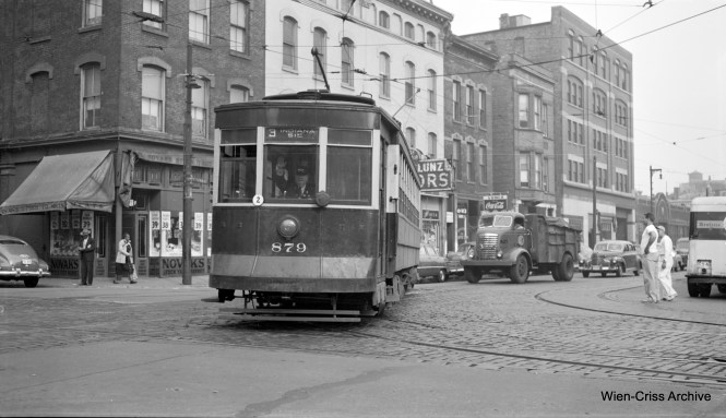 Ther motorman of CTA Pullman 879 waves at the photographer as he rounds the turn from Wells onto Division, running Through Route 3 - Lincoln-Indiana, which was discontinued on March 11, 1951. (Robert Selle Photo, Wien-Criss Archive)