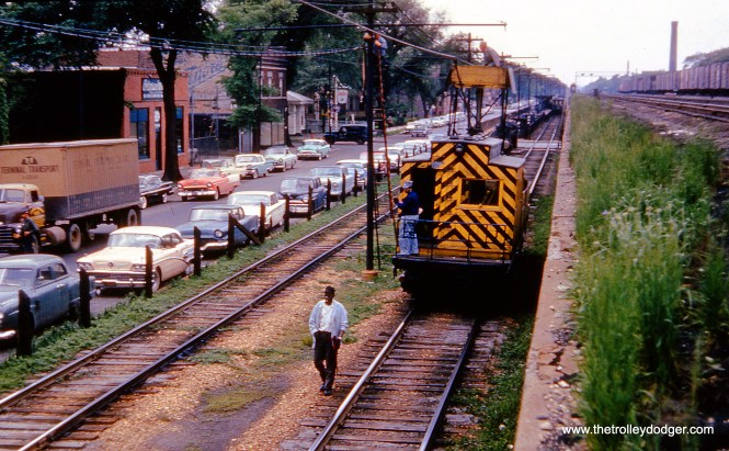 """""""Chicago, IL. Looking westbound on CTA's Lake Street """"L"""" at (South) Lake Street (now Corcoran Place), at Menard Avenue. Line car #S200 is seen doing wire work. In distance is the Austin/Lake """"L"""" station. At right (on embankment) is one-time """"Boulevard"""" Chicago & North Western station (located at Austin Boulevard). May 27, 1960."""" Don Ross: """"S-200 was built by Barney & Smith in 1901 at M-WSER 783. It was renumbered in 1913 as 2783. In 1916 it was rebuilt as a work motor and numbered S-200. It became CRT S-200 in 1924."""""""