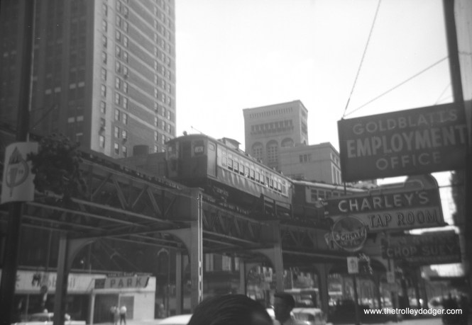 """A two-car train of CTA 4000s, running on the Lake Street """"L"""", are at Wabash and Van Buren on the Loop. In the background, you can see the Auditorium Theater building."""