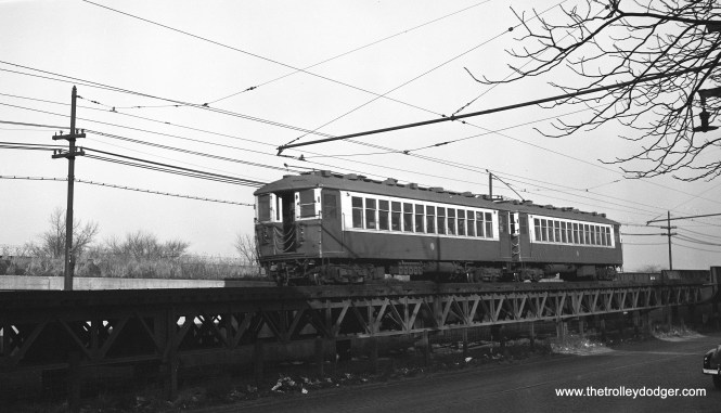 "Two CTA 4000s go up the ramp on Lake Street, just west of Laramie, to rejoin the steel ""L"" structure east of here on November 30, 1952. (Robert Selle Photo)"
