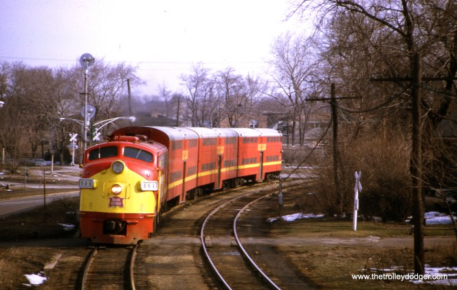 "Westbound Rock Island train #113 at the 91st Street depot on April 5, 1970. Our resident south side epert M. E. adds, ""The caption says this view is ""at the 91st Street depot."" Not quite. The view faces north. The train is curving from west (along 89th St.) to south. Notice the railroad crossing signals and gates in the background. That trackage joined with the CRI&P traffic to the east. On that trackage ran the B&O Capitol Limited on its way to Washington DC, as captured in https://thetrolleydodger.com/wp-content/uploads/2018/07/proofs288.jpg , although in that photo the Capitol Limited is inbound to Chicago."""