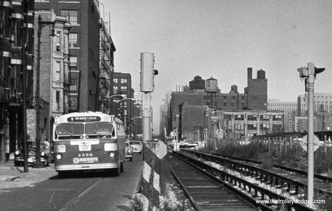 """On August 9, 1953 CTA bus 5306 heads west on Route 6 - Van Buren Street at Racine, next to new temporary Garfield Park """"L"""" trackage that went into service the following month. at right, you can see the existing """"L"""" structure, which was torn down the following year."""
