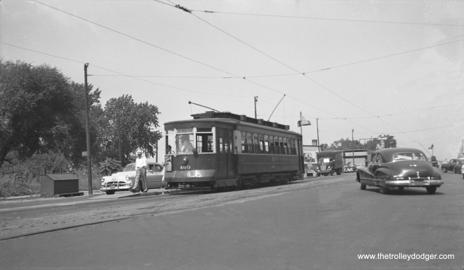 """CTA Pullman 460 is on either Route 8 - Halsted or 9 - Ashland in the early 1950s, you can't quite make it out on the roll sign. However, I am leaning towards Halsted, as Ashland got bussed in 1951, and the auto at left looks more like 1953 vintage. This streetcar was saved by the CTA, and is now at the Illinois Railway Museum. It is one of only three red Pullmans saved, the others being 144 (also at IRM) and 225 (at the Seashore Trolley Museum in Maine). Charles F. Amstein adds that 460 is """"on Ashland, just north of 95th Street, looking north-northwet. I grew up in this area and spent much of my time at Beverly Bowling Lanes, seen in the distance at right."""""""