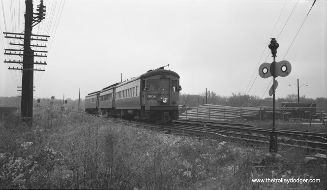 According to the notes the late Robert Selle made for this photograph, taken on October 26, 1958, this is the start of a Central Electric Railfans' Association fantrip. This was more than a year after passenger service had been abandoned on the Chicago Aurora and Elgin interurban. The location is a crossover just east of First Avenue in Maywood, and we are looking mainly to the east. Due to construction of the nearby Eisenhower Expressway, this would have been about as far east as CA&E trains could have gone at this time. Here, the line curved off to the right and headed southeast before crossing the DesPlaines River. Building the highway through that spot meant the CA&E tracks, and bridge, had to be moved slightly north of where they had been. This was all put back in place by 1959, but was never used since the interurban was abandoned. The fantrip train included cars 453 and 430. Mr. Selle did not identify the middle car in his notes, but no doubt it can be determined from other pictures taken on the same trip.