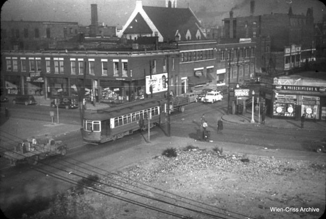 "On November 13, 1950 a northbound Ashland Avenue car, running here on Paulina, crosses Van Buren. The view is from the nearby Marshfield ""L"" station. On September 20, 1953 the CTA put Garfield Park ""L"" trains onto temporary trackage in Van Buren for about 2 1/2 miles, while the Congress Expressway was being built. (William C. Hoffman Photo, Wien-Criss Archive)"