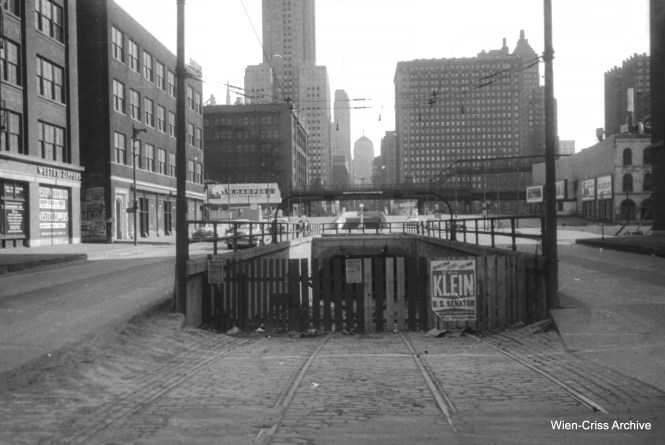 By April 11, 1954, when this picture was taken by the late Bill Hoffman, the LaSalle Street streetcar tunnel had already been closed for about 15 years. It fell victim to subway construction in 1939. But as you can see, the north approach had not yet been filled in. In the background, you can see a different ramp, a block south, which leads to Carroll Avenue. That had been built in 1928 and is often mistaken for the streetcar tunnel entrance. You can find a picture similar to this, taken in 1953 by the late Bob Selle, in my book Building Chicago's Subways. (Wien-Criss Archive)
