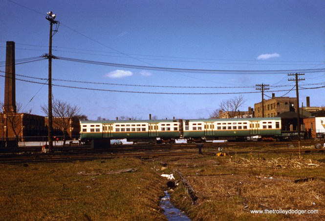 "I presume that this picture, taken on April 13, 1957, shows a CTA Garfield Park ""L"" train near the east end of the Laramie Yard. (between Laramie 5200 W. and Lavergne 5000 W.) Just east of here, there was a ramp going up to the elevated structure that ran downtown. Just south of here, the Congress (now Eisenhower) Expressway was under construction. Laramie Yard, or portions of it, continued in use for about a year after the new Congress median line opened in June 1958. At left, it looks like a school building, but as far as I can tell, none of the structures in the picture still exist. Today, this area is occupied by the Michele Clark Academic Prep Magnet High School, built in the early 1970s."