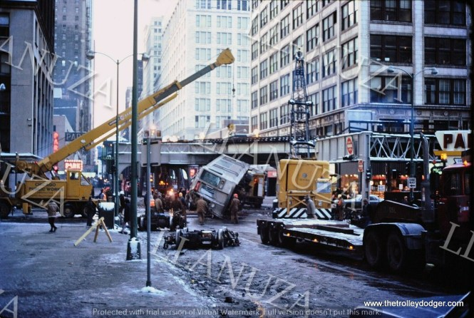 """Accident photos are a sensitive and controversial topic in the railfan field. Some don't think they should be shown at all, while others believe they are an important part of history. This is the aftermath of the 1977 accident where one CTA train ran into another, right at the corner of Wabash and Lake, and pushed some """"L"""" cars off the structure. Since that tragedy, where several people lost their lives, additional steel has been added to the structure to prevent a reoccurence. This is a Mark Llanuza photo."""