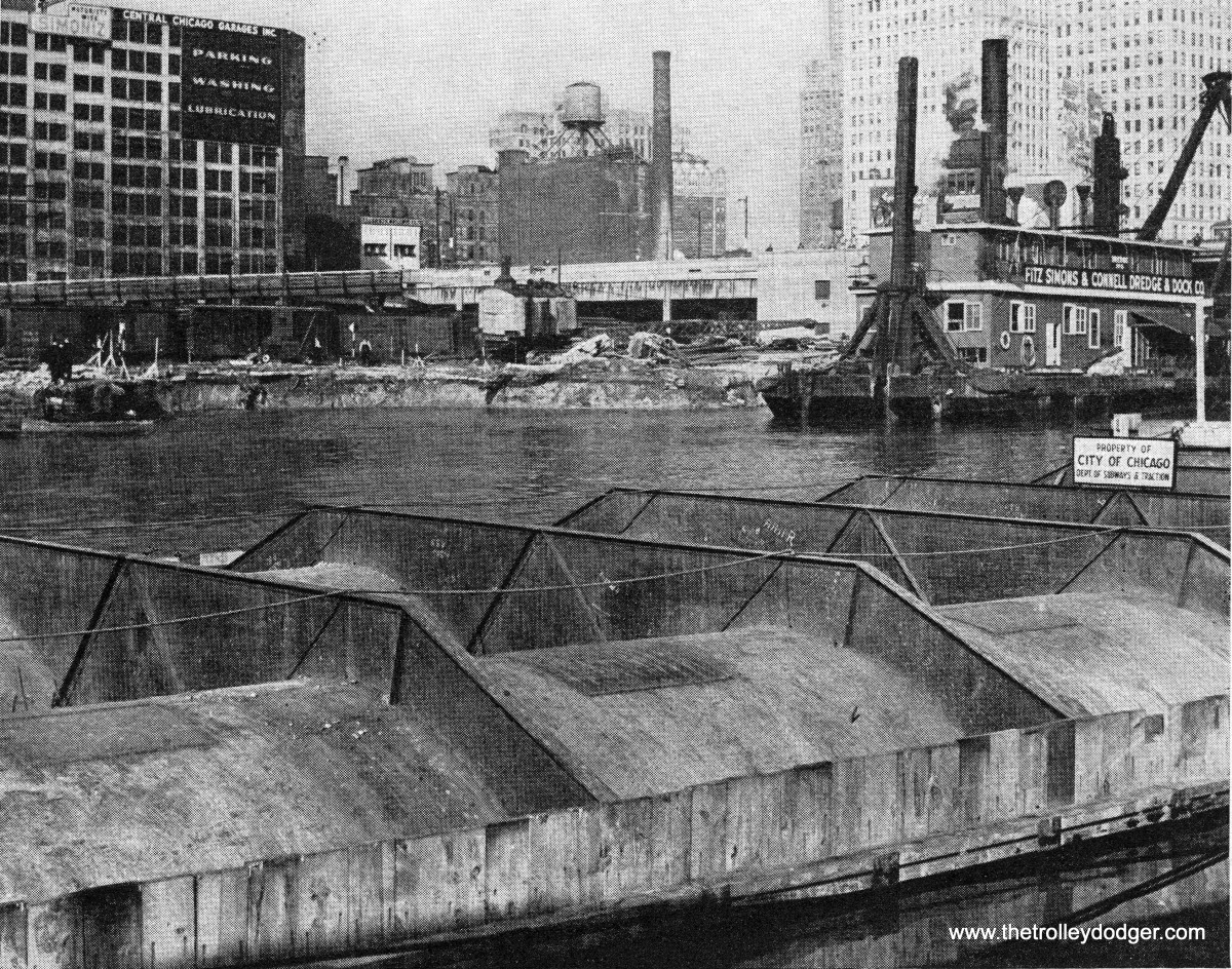 """From Engineering News-Record, November 2, 1939: """"At anchor in the Chicago River after a 15-mile tow up the shore of Lake Michigan is this prefabricated double tube section of Chicago's new subway. Across the stream is an indentation which marks the point where the north end of the tube will connect the land subway now being built. At the time the photograph was taken, the dredge was being moved in to complete removal of the State Street Bridge foundations. See also cover picture."""""""