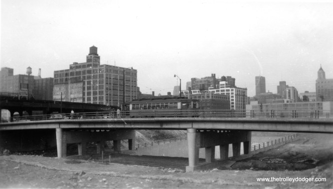 "There was only a short time frame when this picture could have been taken at Halsted and Congress. In the late 1940s, PCCs were used on Halsted, but they were removed starting in 1953, and service ended the following year with older red cars such as this. Under the new bridge, part of the Congress Expressway project, are the subway portals which now serve the rapid transit line that replaced the Garfield Park ""L"" seen at left."