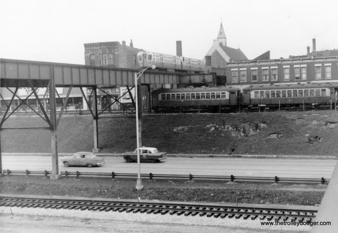 "On February 24, 1957 we see a Douglas Park ""L"" train crossing over a Garfield Park one, running on temporary tracks in Van Buren Street, while the Congress median line (foreground) is under construction."