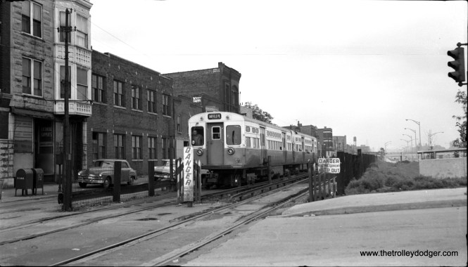 "Around July 1, 1957, a westbound CTA Garfield Park ""L"" train is westbound on the Van Buren temporary trackage. I believe the cross street is California Avenue (2800 W.)."