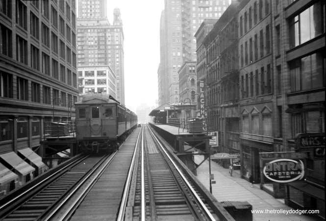 Wood cars at Randolph and Wabash in July 1957. At right, the Kodak Store (133 N. Wabash Avenue) and Blackhawk Restaurant (home of the spinning salad bowl) are visible.