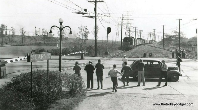 Some fans are shooting a South Shore Line freight in Gary, Indiana. The car looks like about a 1936 Lincoln Zephyr.