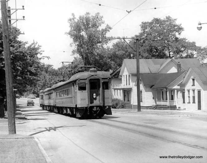 South Shore Line 110 and train running on the street in Michigan City.