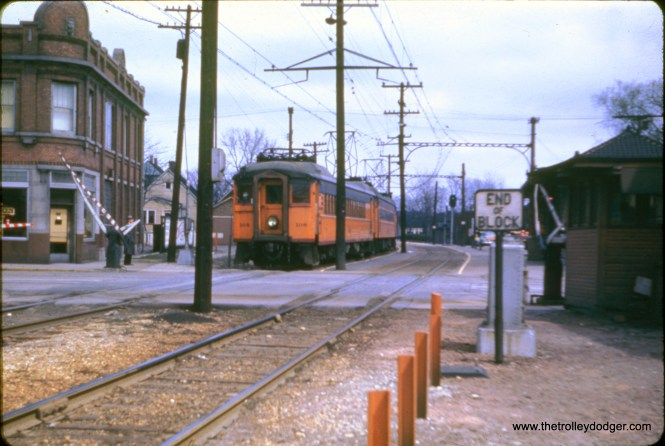 "Mitch Markovitz: ""Westbound (South Shore Line) train at Hammond. Has to be about 1949 as 108 has only been lengthened but not streamlined and air conditioned, and the gates are white and black but not yellow and black. The car behind it has been lengthened and streamlined."""