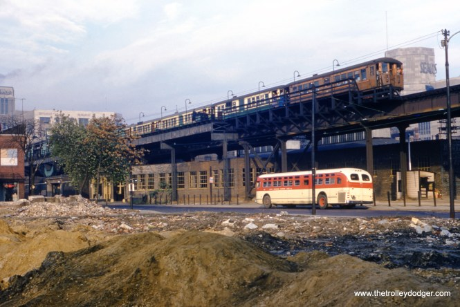"Bill Hoffman's notes: ""October 25, 1954. View northwest - Halsted Street station - Englewood ""L"" line - (63rd Place). Old Chicago & Interurban Traction terminal in foreground."" Our resident south side expert M.E. adds: ""Lots of things to say about this picture. (1) The first car has the old Rapid Transit System paint job. It seems to me that, when the CTA formed married pairs of L cars, they would have repainted the CRT car in current CTA livery. So I think the cars on this train were not married pairs. (2) Notice the eastbound train, which is stopped, extends past the platform. I think the rear of the train also extends past the rear of the platform. Why? Until 1949, Normal park L cars were attached or detached from mainline Englewood trains at Harvard. Therefore, Englewood trains west of Harvard had one less car than trains had east of Harvard. But after 1949, when Normal Park service became a shuttle to and from Harvard, all Englewood trains had the same number of cars both west and east of Harvard. I think the train shown has 7 cars. One reason, of course, is the CRT paint on only one car. A second reason is that, as I recall, platform lengths back then accommodated 6 cars. Therefore the first and seventh cars would extend past the platform. A third factor would be if there were still multiple conductors who stood between cars to open and close entry and exit doors. There would be no conductor at the rear of the train, and no conductor at the front. So the train could extend past the platform at both ends. But if, by then, there were indeed married pairs and only one conductor who controlled all the doors, then why is only the first car still painted in CRT colors? Too bad we can't count the cars. (3) The bus shown belonged to the South Suburban Safeway Lines, which essentially replaced the Chicago & Interurban Traction Co. and kept the same route along Halsted St. into Chicago, ending on the south side of the 63rd and Halsted L station. But in the meantime, the bus company started a second route north of Harvey that used Dixie Highway, Western Ave., and 63rd St., and ended at the 63rd/Halsted L. So the SSL bus shown could be on either the Halsted line or the Western line. The other bus line that served 63rd/Halsted was the Suburban Transit System, based in Oak Lawn. All this bus service came to Englewood because the shopping district centered around 63rd and Halsted was the largest outside the Loop. (4) Landmark buildings in the picture: (a) The Sears store was on the northeast corner of 63rd and Halsted. (b) The tower at the far left was atop the Wieboldt store on the southwest corner of 63rd and Green (a half-block west of Halsted). (5) West of the interurban building, and just past the tree, is the Rapid Transit station entrance from 63rd Place. There was also an entrance on Halsted St. (6) The red neon sign at the left seems to say ""Ambulances"". I don't know what that was about. (7) This picture was made possible because the buildings on the south side of 63rd Place had been razed, leaving a mound of dirt and rocks."" Andre Kristopans adds: ""You are correct the shot at 63/Halsted has odd number of cars, and therefore can't be consecutive numbers. As I understand, the plushies were paired up starting in 1950s, but baldies never really were. There was an effort made circa 1949, but until the end there were mismates. It was only after the plushies came off Lake and went to Ravenswood 1964 was there really an effort to keep pairs together. Remember there were trailers around until about 1960, so you had to pair a trailer with a motor both on Lake and Evanston. Also, ""CTA""ing 4000s was a multi-part process. Install MUDC, convert from line to battery control, add permanent markers, add headlights, repaint. Not all at same time. Have seen photos of cars in brown with marker boxes and headlights and cars in green without. Another item - how were train splits handled? There were at least three locations where in-service trains were split. Harvard on Englewood, Laramie on Garfield, Damen on Logan Square. I assume a fresh crew of two handled the cut section, shuttling Harvard to 69, Laramie to 22/Mannheim (or Roosevelt) and Damen to Lawndale, with one guard going off duty at the cut location and going back on aboard the next inbound train. Also there were cuts and adds at midroute yards, but that was simply the guards on the cut or add ending there. Finally, there were thru Jackson Park trains to Linden rush hours until the reorganization. Probably only part of train went thru, with rest being added to a southbound at Howard? Howard was not a major yard until 1950s apparently, Wilson was."""