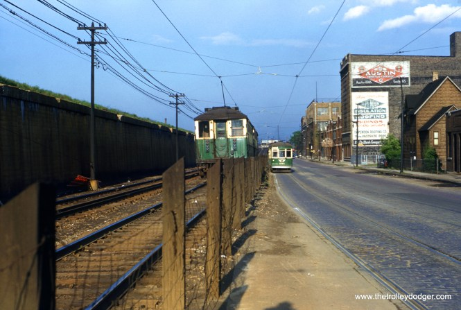 "When the Lake Street ""L"" ran at ground level west of Laramie, it ran parallel with the Lake Street streetcar line for a few blocks, before the latter crossed over to the north side of the railroad embankment at Pine Avenue. On May 8, 1954, about three weeks before buses replaced streetcars on CTA Route 16, westbound car 3163 passes an eastbound ""L"" train made up of 4000s. Note the trolley wires for both used a common support. The ""L"" was relocated onto the embankment on October 28, 1962. (William C. Hoffman Photo)"
