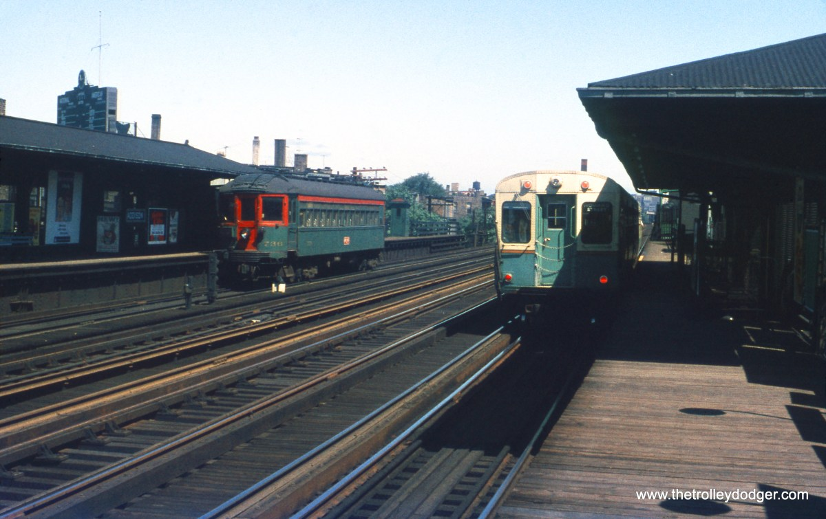 A southbound North Shore Line train (car 736) and a northbound CTA train are at Addison Street on July 29, 1956. The Wrigley Field scoreboard is at left. This station was rebuilt in 1994 with a center island platform. The Cubs were out of town, and lost both ends of a double-header to the Philadelphia Phillies that day. (William C. Hoffman Photo)