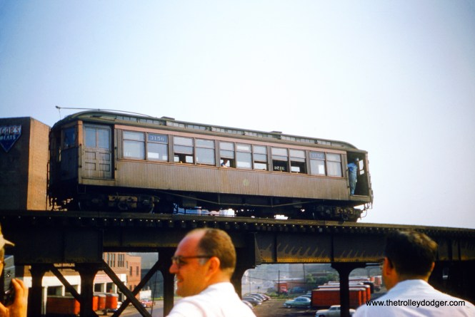 "CTA 3156, seen here on the Stock Yards branch in the early 1950s, was built by Brill in 1909 for the Lake Street ""L"". After it was no longer needed there, it was used on this shuttle operation in the early-to-mid 1950s, still sporting at least one trolley pole. I am not sure of the exact location here, but it is nearby Agar's Meats and on a section of ""L"" that was double-tracked. The men in the foreground were either on the roof of a nearby building, or perhaps on the Chicago Junction Railway embankment, if that was close by. (Wendell E. Grove Photo)"