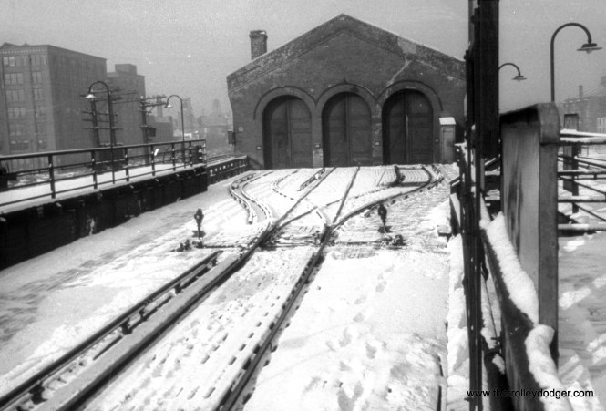 """This started out as an Anscocolor slide, but there was so little color left in it that I had no choice but to convert it to black-and-white. This is the view looking west from the Racine """"L"""" station, on the Met main line, on February 26, 1954, showing a three-point switch leading to the Throop Street Shops, which would be demolished within a few months. While Garfield Park trains no longer took this path, Douglas Park trains still did, until April 1954, when that line was re-routed downtown via the Lake Street """"L"""". (William C. Hoffman Photo)"""