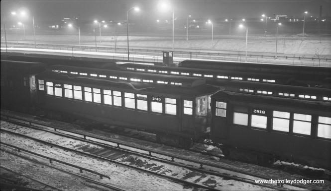 """A night shot of CTA 2810 and 2818 in the Laramie Yards on February 1, 1957. By then, the Congress Expressway was open as far as Laramie and was adjacent to the Garfield Park """"L"""". It was still under construction west of here, and the """"L"""" ran on temporary trackage. (Robert Selle Photo)"""